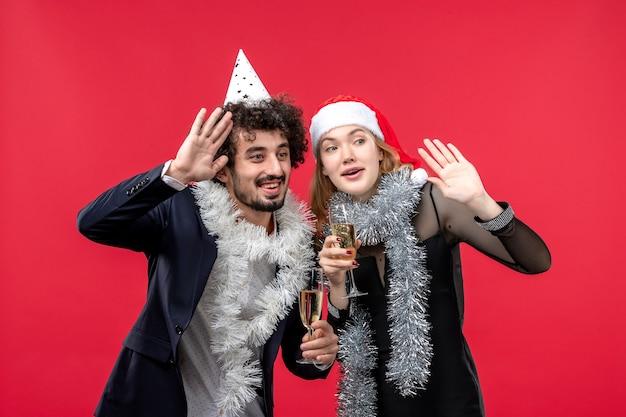 Giovani coppie felici di vista frontale che celebrano il nuovo anno sull'amore rosso di natale della foto del pavimento