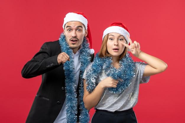 赤い壁の色のクリスマスの愛の新年の気分で若い幸せなカップルの正面図