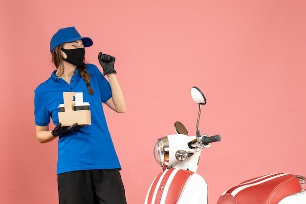 Vista frontale della giovane ragazza corriere felice che indossa guanti con maschera medica in piedi accanto alla moto con in mano piccole torte di caffè su sfondo color pesca pastello