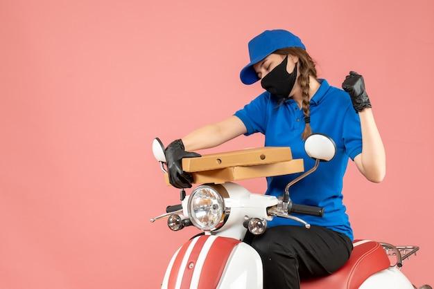 Vista frontale del giovane corriere femminile emotivo felice che indossa maschera medica e guanti seduto su uno scooter che consegna ordini su sfondo pesca pastello pastel