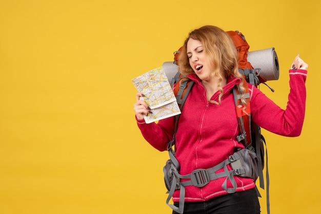 Vista frontale della giovane ragazza in viaggio felice in mascherina medica raccogliendo i suoi bagagli e tenendo la mappa godendo il suo successo