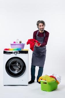 白い壁の洗濯機の近くに立っている赤いタオルを保持している正面図若い家政婦の男