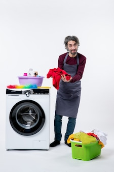 Front view young housekeeper man holding red towel standing near washing machine on white wall