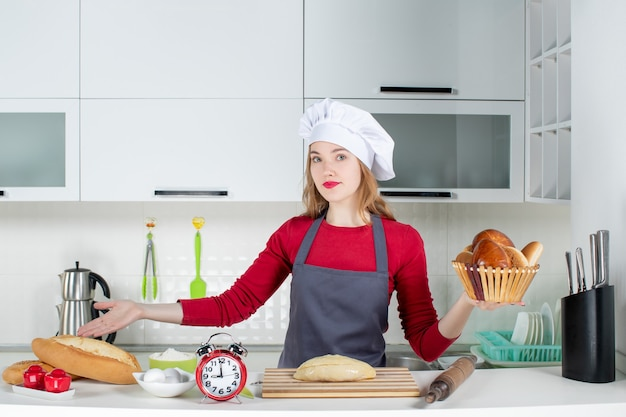 Front view young housewife in cook hat and apron holding basket with loaf in the kitchen