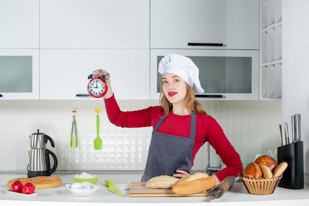 Vista frontale giovane casalinga con cappello da cuoco e grembiule che tiene sveglia rossa in cucina