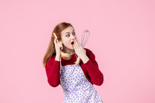 ピンクの背景に泡立て器と木のスプーンを保持している正面図若い主婦料理専門職水平パイ女性料理均一なケーキ生地