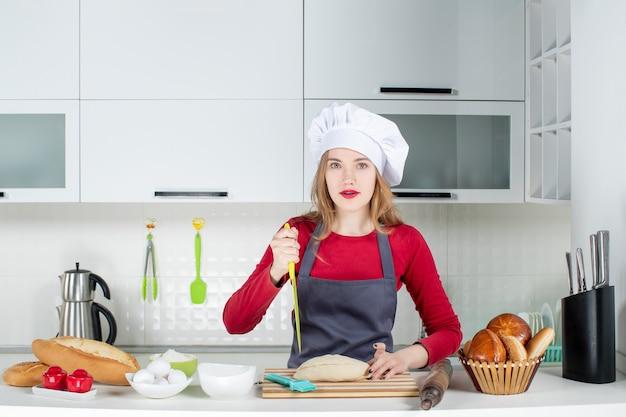 料理の帽子とエプロンでキッチンでパンを切る正面図