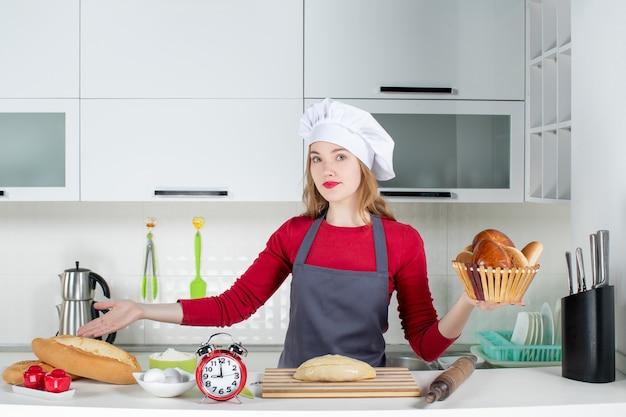 Вид спереди молодая домохозяйка в поварской шляпе и фартуке, держащая корзину с буханкой на кухне