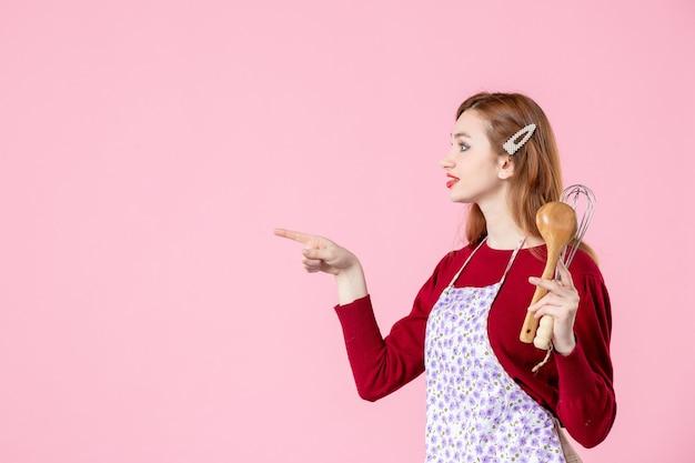 Вид спереди молодая домохозяйка позирует с ложкой и венчиком на розовом фоне сладкая еда торт пирог тесто готовка кухня женщина цвет