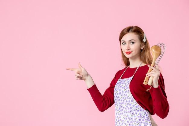 正面図ピンクの背景にスプーンとウィスクを持つ若い主婦甘い色の食品ケーキパイ生地調理キッチンの女性