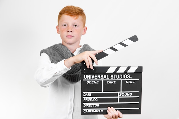 Front view young kid with clapperboard