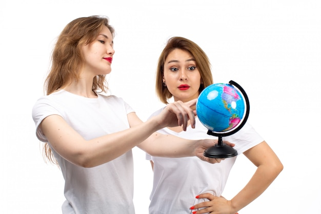 A front view young ladies in white t-shirts holding little round globe on the white