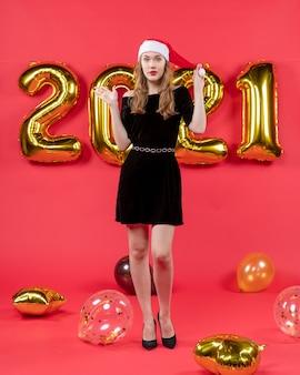 Vista frontale giovane donna in abito nero palloncini sulla foto rossa del nuovo anno