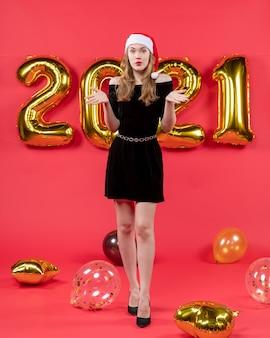 Vista frontale giovane donna in abito nero palloncini su rosso