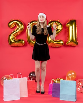 Front view young lady in black dress closing eyes bags on floor balloons on red
