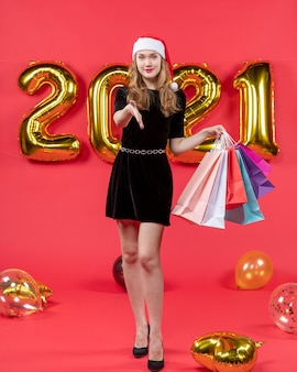 Front view young lady in black dress giving hand holding shopping bags balloons on red