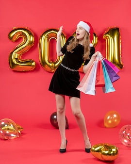 Front view young lady in black dress hailing somebody holding shopping bags balloons on red