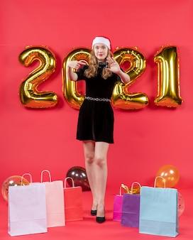 Vista frontale giovane donna in abito nero che tiene la carta nelle sue borse a mano su palloncini sul pavimento su rosso