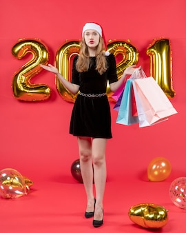 Front view young lady in black dress holding shopping bags balloons on red