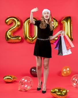 Vista frontale giovane donna in abito nero con in mano le borse della spesa che chiamano qualcuno palloncini sul rosso