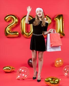 Vista frontale giovane donna in abito nero con in mano le borse della spesa che saluta qualcuno con palloncini sul rosso