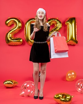 Front view young lady in black dress holding shopping bags pointing at camera balloons on red