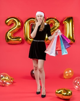Front view young lady in black dress holding shopping bags putting hand on her mouth balloons on red