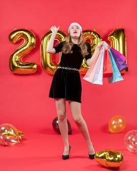 Vista frontale giovane donna in abito nero che guarda il soffitto che tiene in mano i palloncini delle borse della spesa su rosso