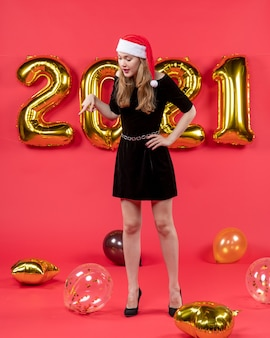 Vista frontale giovane donna in abito nero che guarda i palloncini sul pavimento su rosso