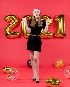 Front view young lady in black dress looking up opening hand balloons on red