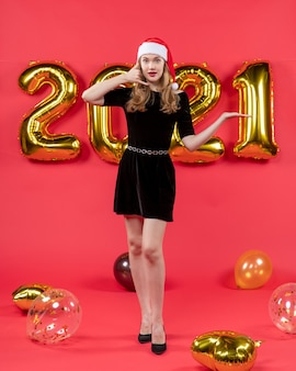 Front view young lady in black dress making call me phone sign balloons on red