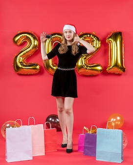 Front view young lady in black dress making call me phone sign holding card bags on floor balloons on red