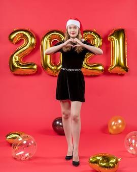Vista frontale giovane donna in abito nero che fa il segno del cuore con le dita palloncini sul rosso