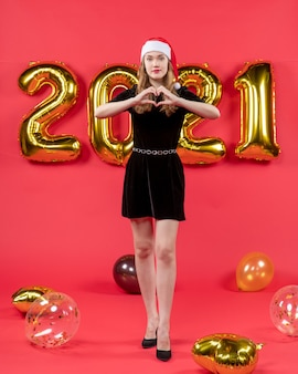 Front view young lady in black dress making heart with fingers balloons on red