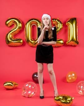 Vista frontale giovane donna in abito nero che fa segno shh palloncini sul rosso