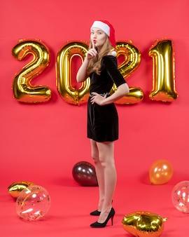 Vista frontale giovane donna in abito nero che fa segno shh mettendo la mano su un palloncino in vita sul rosso