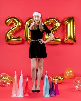 Front view young lady in black dress pointing at camera bags on floor balloons on red