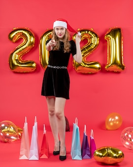 Front view young lady in black dress pointing at camera balloons on red