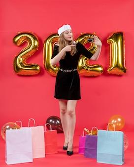 Giovane donna vista frontale in abito nero che indica i sacchetti di carta sui palloncini sul pavimento su rosso
