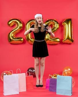 Giovane donna vista frontale in abito nero che indica le sue borse a mano su palloncini sul pavimento su rosso