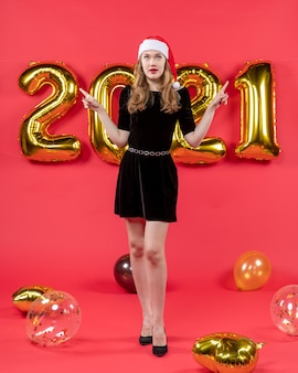 Front view young lady in black dress pointing at something balloons on red