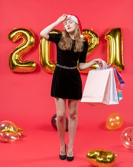 Front view young lady in black dress putting hand to her head holding shopping bags balloons on red
