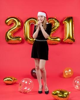 Giovane donna vista frontale in abito nero che si mette le mani sulla bocca palloncini sul rosso