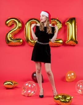 Vista frontale giovane donna in abito nero che mette le mani sulle spalle palloncini sul rosso
