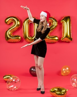 Front view young lady in black dress showing size with hands balloons on red