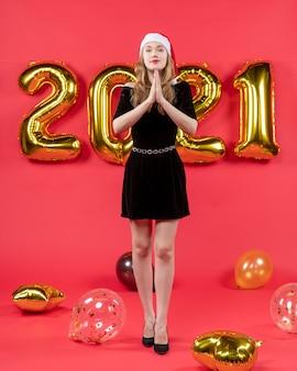 Vista frontale giovane donna in abito nero che adora palloncini su rosso