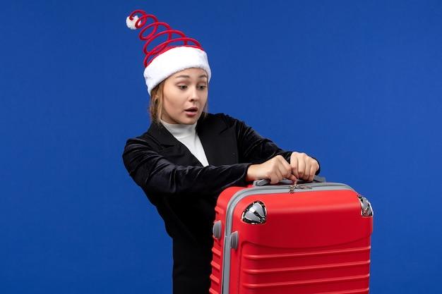 Giovane signora di vista frontale che trasporta la grande borsa rossa sulla vacanza di vacanze di capodanno di colore della parete blu
