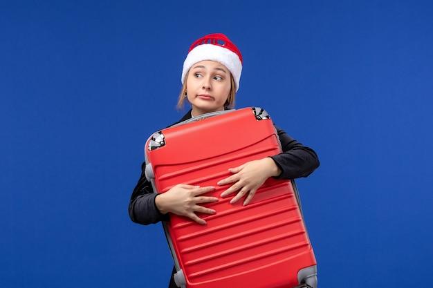 La giovane signora di vista frontale che trasporta la grande borsa rossa sulla parete blu colora la vacanza di festa del nuovo anno