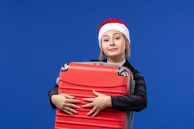 Giovane signora di vista frontale che trasporta la grande borsa rossa sul viaggio di festa del nuovo anno della parete blu