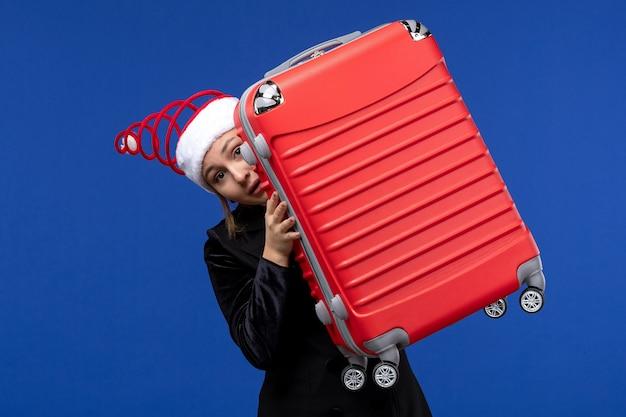 青い机の色の新年の休日の休暇で大きな赤いバッグを運ぶ正面図の若い女性